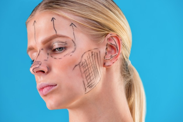 미용사는 여자 얼굴에 교정 라인을 그립니다. 성형 수술 전. 파란색에 격리.