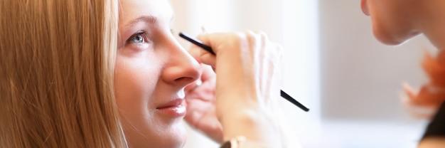 Косметолог рисует модельные брови на лице модели
