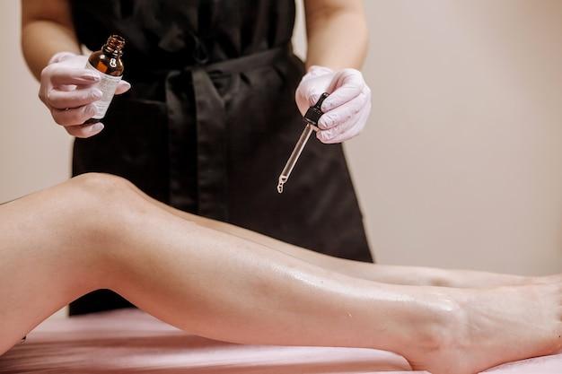 Косметолог капает масло на ноги после эпиляции. концепция депиляции.