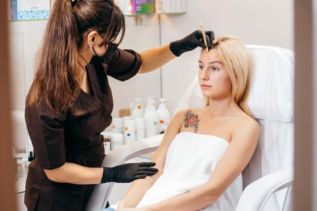 美容師の女性は化粧品キャビネットの美しいモデルの眉毛の矯正を行います