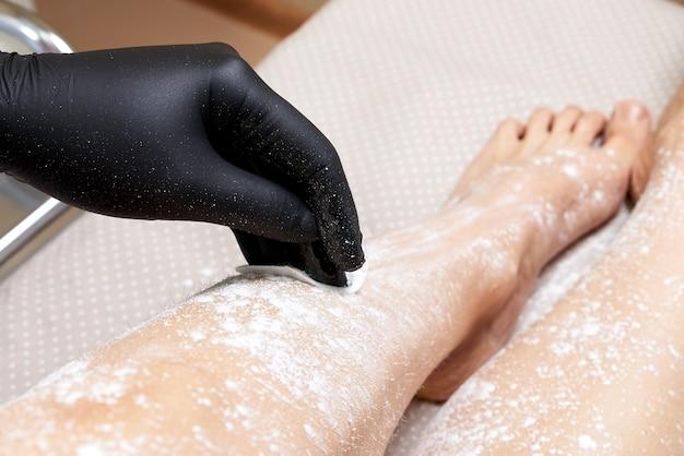 スパセンターで女性の足にワックスを塗る準備をしている美容師。脱毛の準備、白い粉をつける