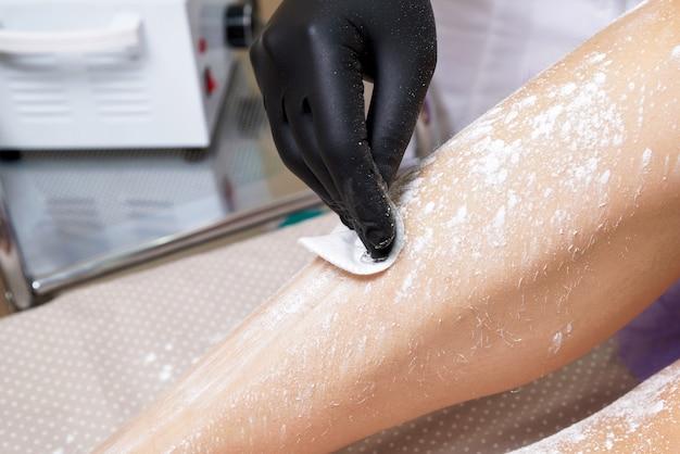 Косметолог готовится восковые женские ноги в спа-центре. подготовка к депиляции, нанесение белой пудры
