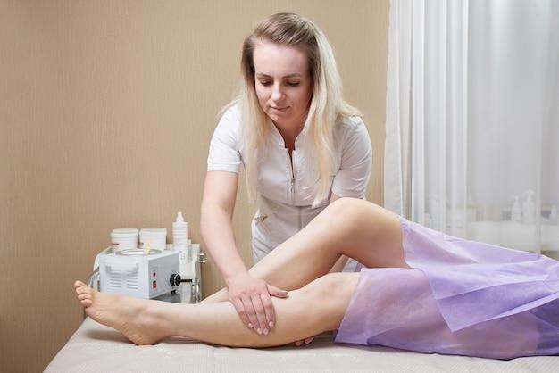 スパセンターで女性の足にワックスを塗る準備をしている美容師。脱毛の準備