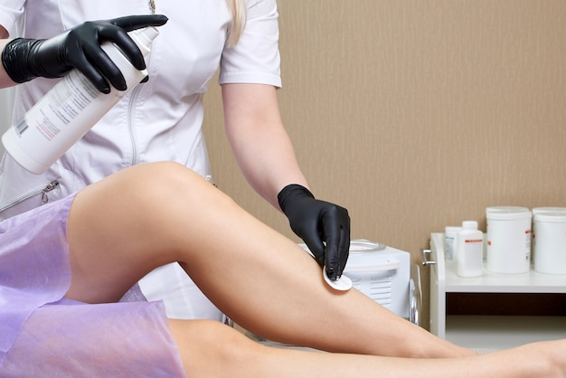 スパセンターで女性の脚にワックスを塗る準備をしている美容師。脱毛の準備