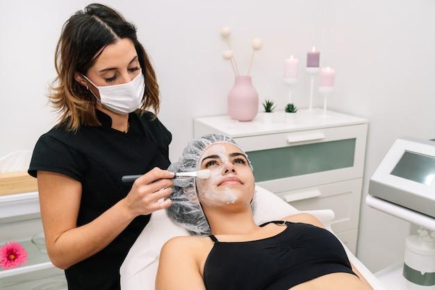 Косметолог делает маску для лица красивой молодой женщине, наслаждающейся в салоне красоты и носящей защитную маску для лица