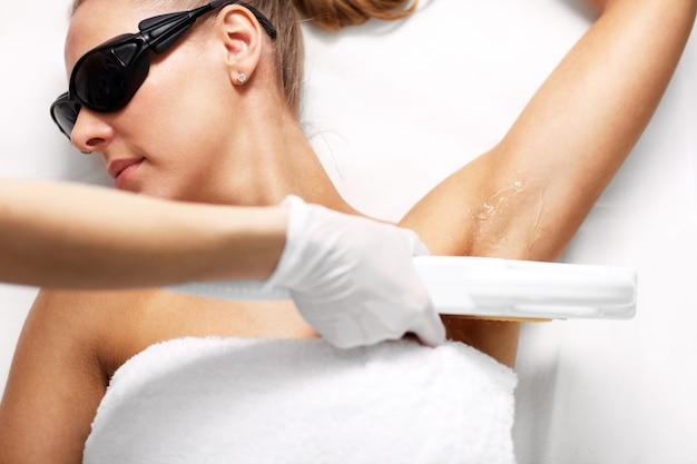 脇の下の女性に脱毛レーザー治療を与える美容師