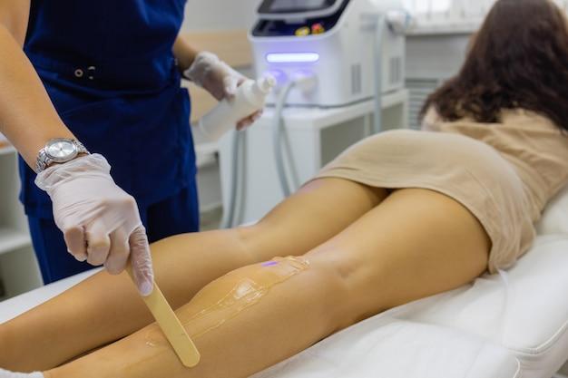 Косметолог дает лечение лазером эпиляции женщине на бедре.