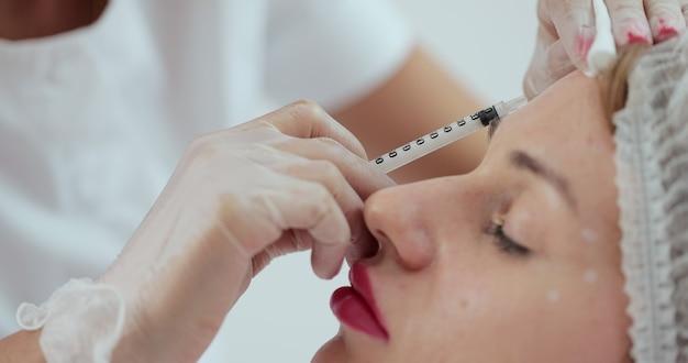 이마에 여성 환자 주사를 주는 미용사. 미용사는 주름, 클로즈업에 대해 여성 이마에 보툴리눔 주사를 만듭니다.