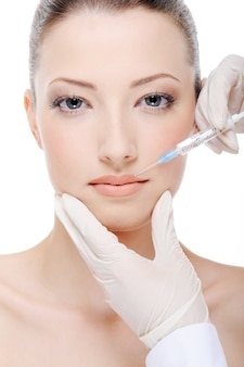 Beautician giving  injection of botox on female lips
