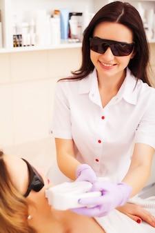 Косметолог дает лечение лазерной эпиляции лицу молодой женщины в клинике красоты.