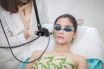 若い女性の顔にレーザー脱毛治療を与える美容師