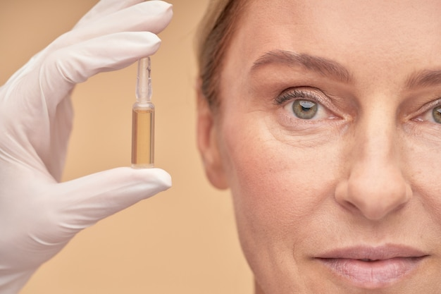 Beautician in a glove holding an ampoule with hyaluronic acid