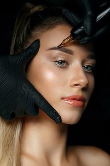 Косметолог рука, применяя перманентный макияж бровей на лице красивой женщины
