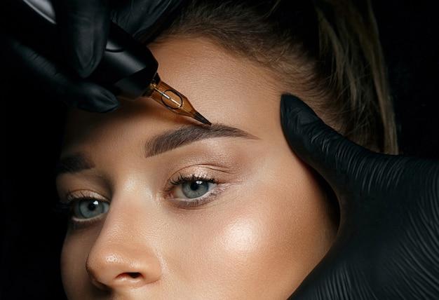 Рука косметолога делает перманентный макияж бровей на привлекательном женском лице