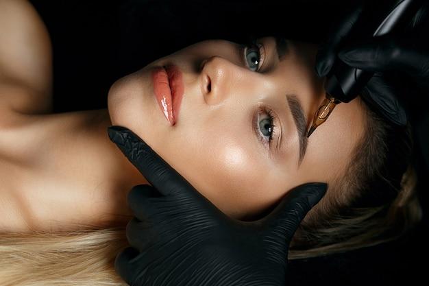 Рука косметолога делает перманентный макияж бровей на лице красивой женщины