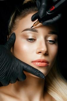 女性の眉毛に眉毛の入れ墨をしている美容師の手。クローズアップショット