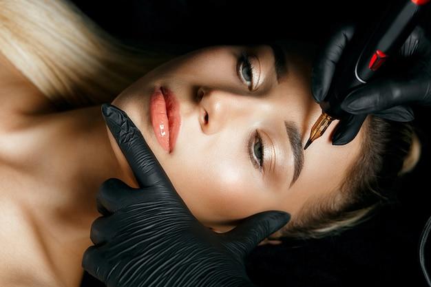 女性の眉毛に眉毛の入れ墨をしている美容師の手