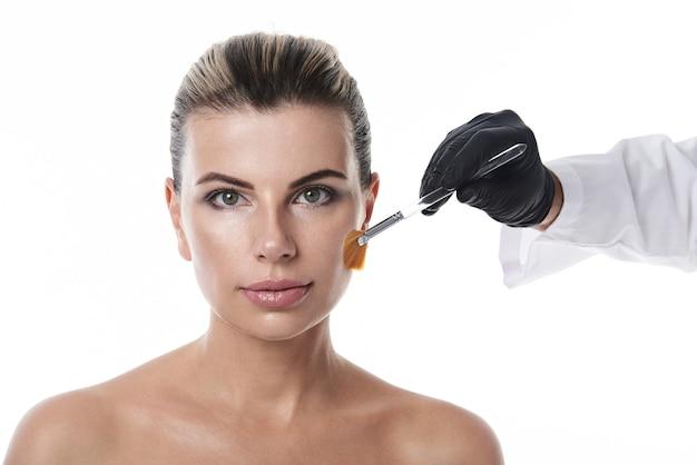 Рука косметолога в черной медицинской перчатке, держащая косметическую кисть на лице привлекательной обнаженной женщины