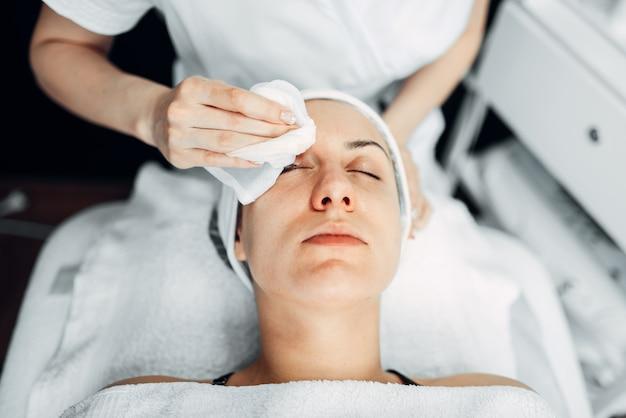 美容師は女性患者の顔、トップビューに手します。