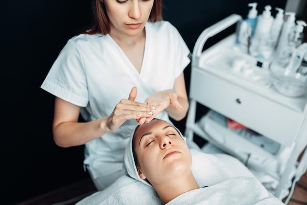 Косметолог руки с кремом против лица пациента