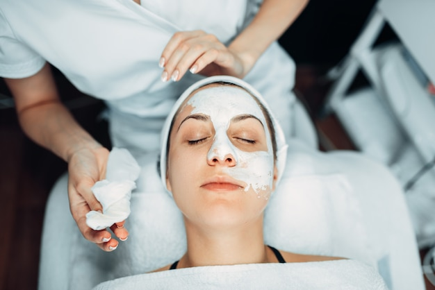 Beautician hands with cream against patient face