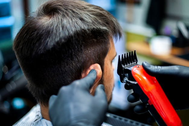 Beautician holding ear for haircut