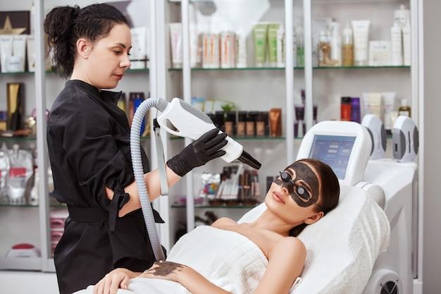 Косметолог держит машину возле лица женщины, покрытой угольной маской в спа-салоне, женщина получает лечение лица лазером в клинике красоты