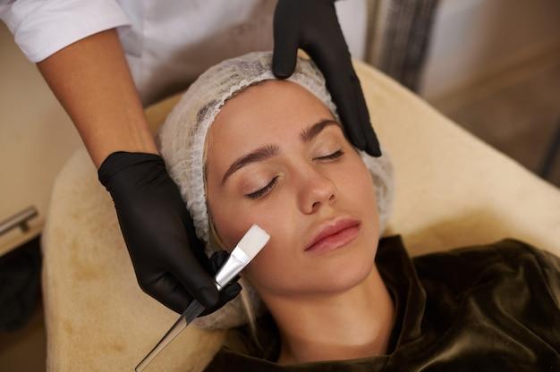 미용사는 스파 살롱에서 얼굴 치료를하는 동안 편안한 아름다운 백인 금발 여자의 얼굴 근처에 브러시를 보유하고