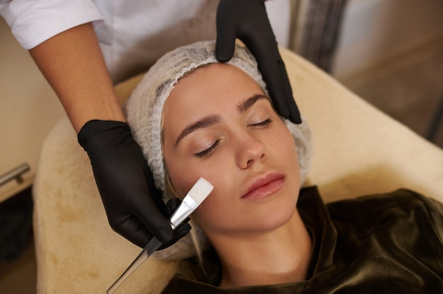 Beautician holds a brush near the face of a beautiful caucasian blonde woman relaxing during face treatment at spa salon