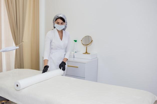 흰색 제복을 입은 미용사는 사무실에서 일회용 기저귀로 소파를 덮는다