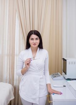 흰색 제복을 입은 미용사는 사무실에서 얼굴을 청소하기 위한 도구를 들고 서 있다