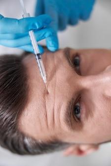 Косметолог в синих перчатках делает инъекцию лифтинг-наполнителя пациенту-мужчине с морщинистым лбом