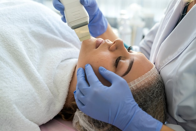Косметолог в синих перчатках делает процедуру ультразвуковой чистки лица молодой пациентке. аппаратная косметология.