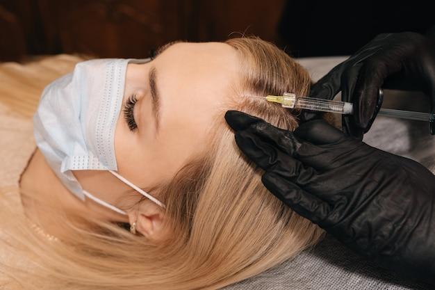 Косметолог в перчатках делает укол в голову блондинке. мезотерапия, терапия от выпадения волос. концепция восстановления волос.