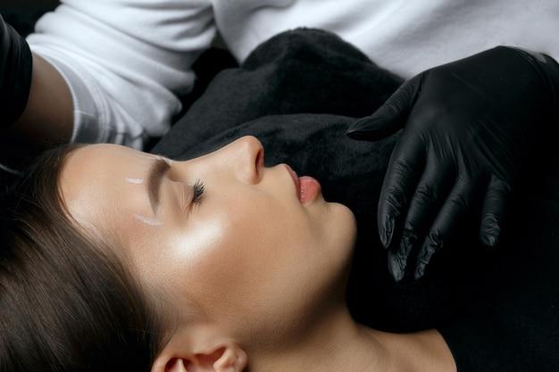 眉毛の恒久的な手順の前に白いマークアップを作る手袋の美容師