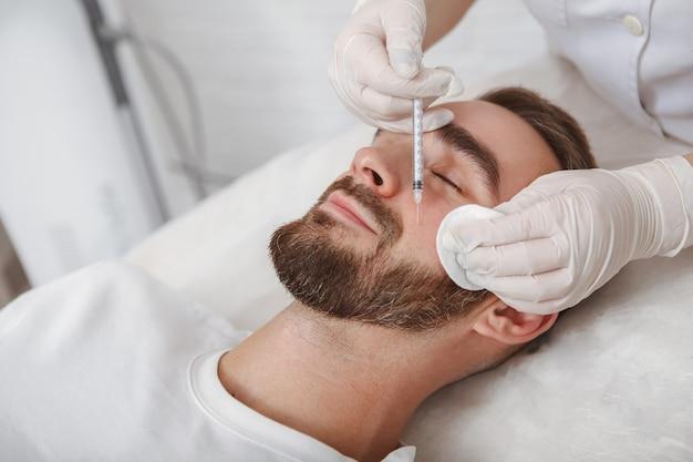 男性クライアントの顔のしわにフィラーを注入する美容師