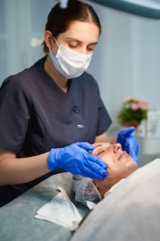 Beautician is applying healthy cream on female facial skin