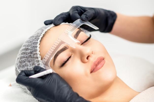 Косметолог измеряет брови линейкой перед татуировкой бровей