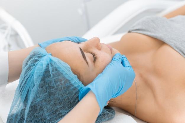Косметолог делает молодой красивой девушке расслабляющий и оздоровительный массаж лица