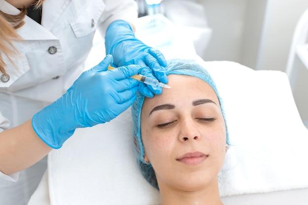 Косметолог делает уколы красоты в кожу молодой красивой девушки