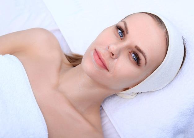 미용사는 아름다운 소녀를 위해 클렌징 및 각질 제거 얼굴을 만듭니다. 미용실.