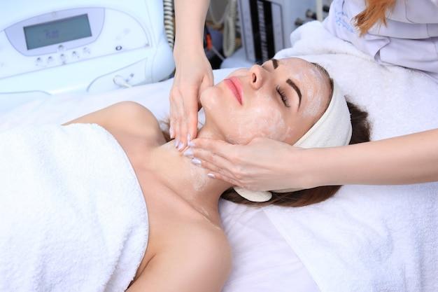 Косметолог делает для красивой девушки очищение и отшелушивание кожи лица. салон красоты.
