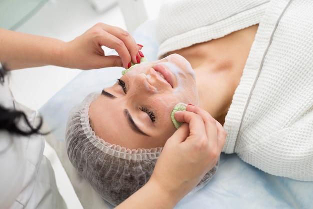 Косметолог делает красивой девушке очищающую и отшелушивающую кожу лица. салон красоты.