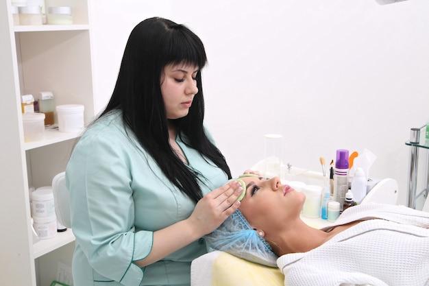 Косметолог делает очищение и отшелушивание лица красивой девушке
