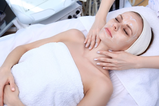 Beautician makes cleansing, exfoliation, massage in a beauty salon.