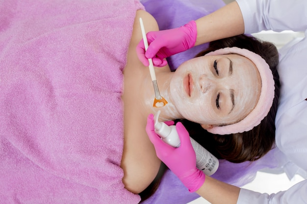 Beautician makes a face clay mask against acne on the face of a woman to rejuvenate the skin. cosmetology treatment of problem skin on the face and body.