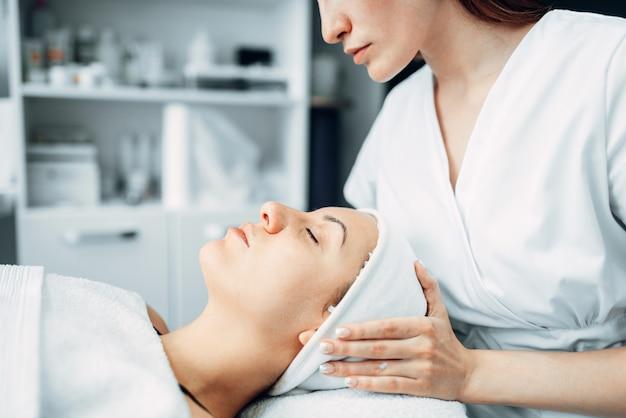 美容師は女性の患者に顔のマッサージを行います