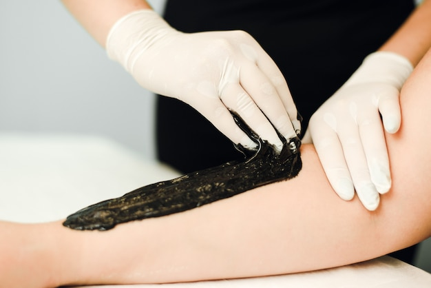A beautician makes hair removal for clean
