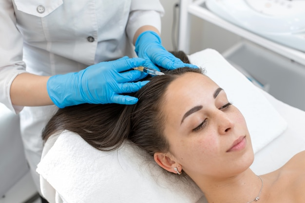 Beautician makes injections of vitamins into the scalp for strengthening the hair