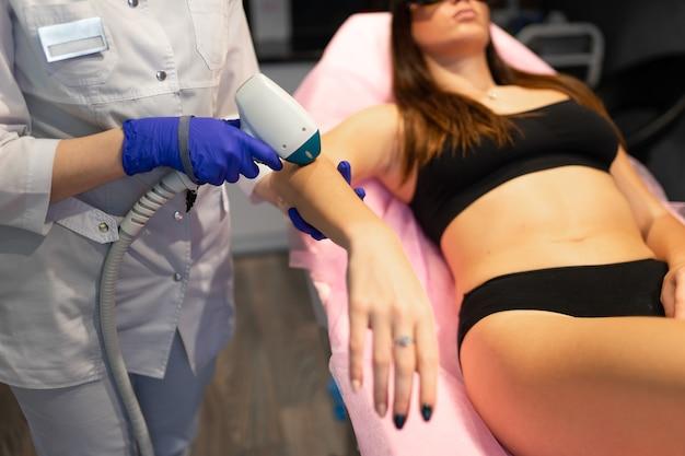 Косметолог делает процедуру лазерной эпиляции